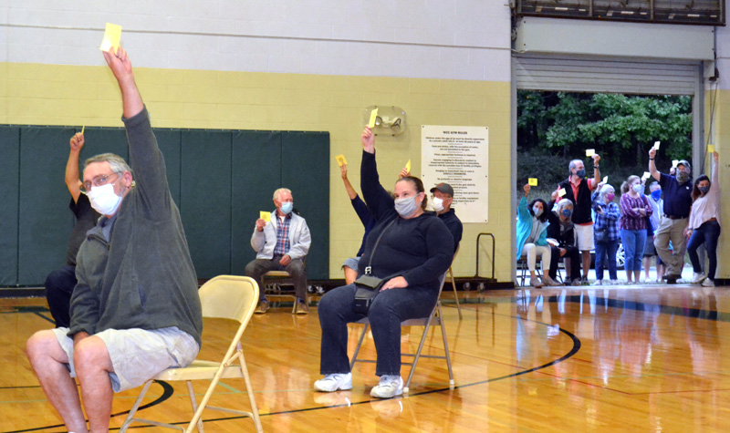 Voters inside and outside the Wiscasset Community Center gymnasium raise their cards to support the Wiscasset Parks and Recreation Department's budget during a special town meeting Thursday, Sept. 17. (Charlotte Boynton photo)