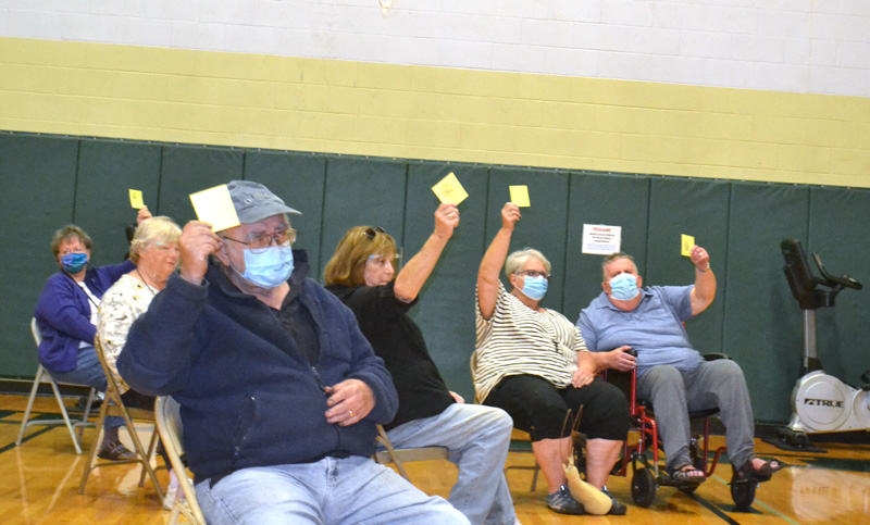 Voters hold up their cards to approve the Wiscasset Parks and Recreation Department's budget during a special town meeting at the community center, Thursday, Sept. 17. (Charlotte Boynton photo)