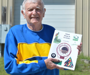 """Walter White, of Waldoboro, holds a copy of his second sports history book, """"Island Hoops & Scratches,"""" which is about playing basketball and billiards on Vinalhaven. (Paula Roberts photo)"""