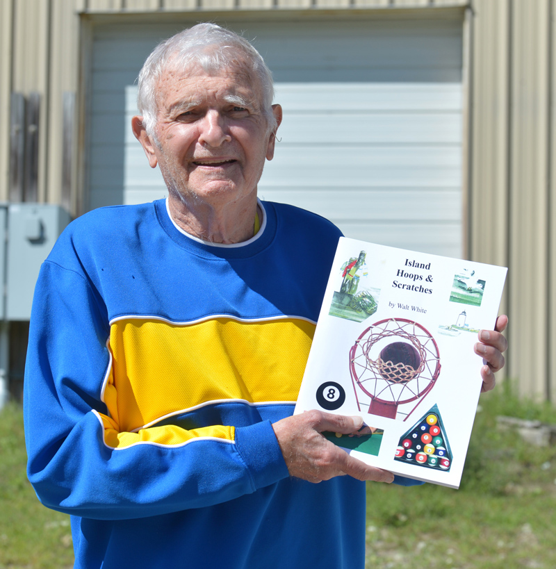 "Walter White, of Waldoboro, holds a copy of his second sports history book, ""Island Hoops & Scratches,"" which is about playing basketball and billiards on Vinalhaven. (Paula Roberts photo)"