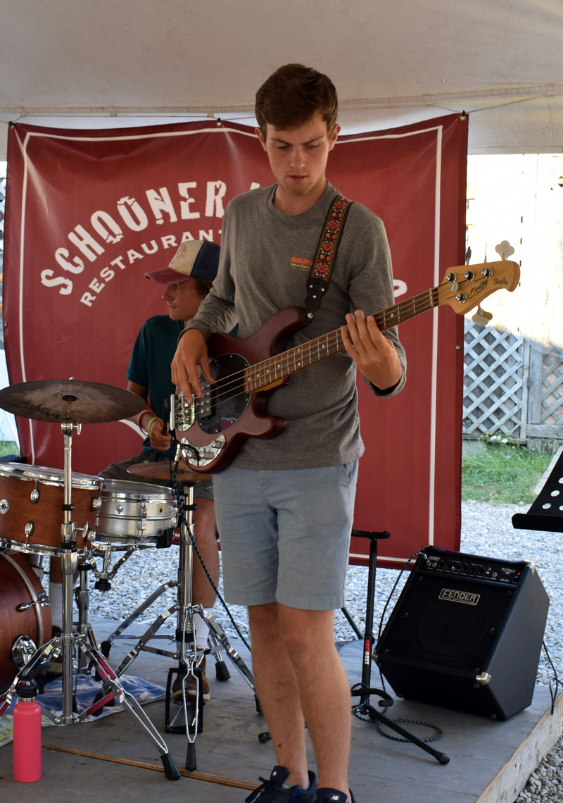 Ben Clifford plays the bass while his cousin, Nick Clifford, plays drums with the band Wharf Cats at Schooner Landing in Damariscotta on Aug. 8. The band formed in the summer of 2019 to honor the late jazz clarinetist Pete Collins. (Evan Houk photo)