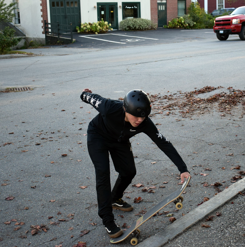 Isaac Rich, a 14-year-old student at Great Salt Bay Community School, picks up his skateboard near the corner of Hodgdon and Church streets in Damariscotta on Monday, Oct. 5. (Evan Houk photo)