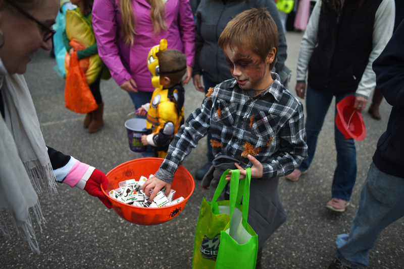 Mitchell Collins, of Round Pond, dressed as a werewolf, gets some Junior Mints from Lisa Pinkham during a trunk-or-treat event at Great Salt Bay Community School in Damariscotta on Oct. 31, 2018. (LCN file photo)