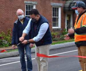 Newcastle Town Manager Jon Duke cuts the ribbon at the base of Academy Hill Road as Selectman Rob Nelson (left) and Road Commissioner Seth Hagar look on. (Evan Houk photo)