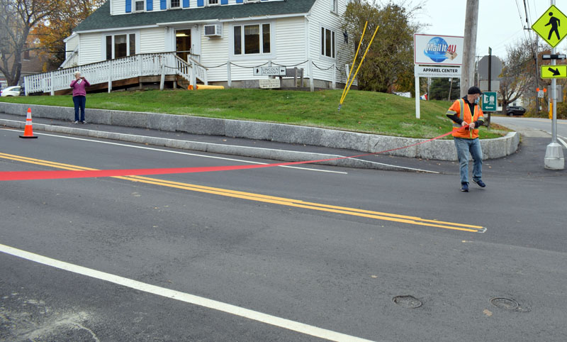 An employee of Hagar Enterprises Inc. sets up a ribbon at the base of Academy Hill Road in Newcastle for a ribbon-cutting ceremony, Thursday, Oct. 29. The Damariscotta-based contractor recently completed the nearly $2 million project. (Evan Houk photo)