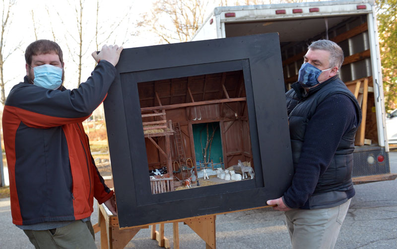 Allan Roberts and Justin Day carry Jake Day's barn diorama. The dioramas can be seen in the windows at Milling Around and the Damariscotta Region Chamber of Commerce. (Paula Roberts photo)