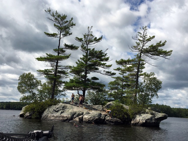 Kids explore the rocks of a small island in Biscay Pond. (Photo courtesy Mary Berger)
