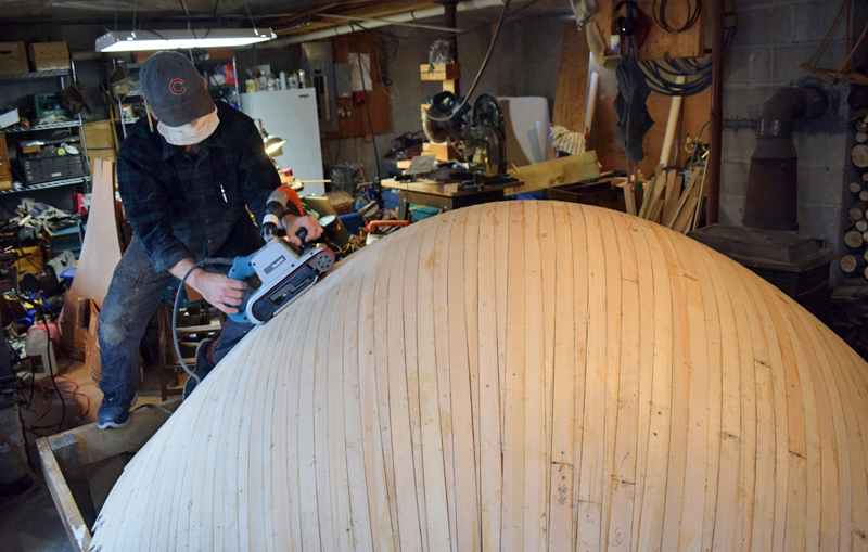 Bristol woodworker Darin Carlucci sands a wooden parabolic bowl in his home workshop on Monday, Dec. 14. A New Hampshire science center will use the bowl to demonstrate the superb hearing of owls. (Evan Houk photo)