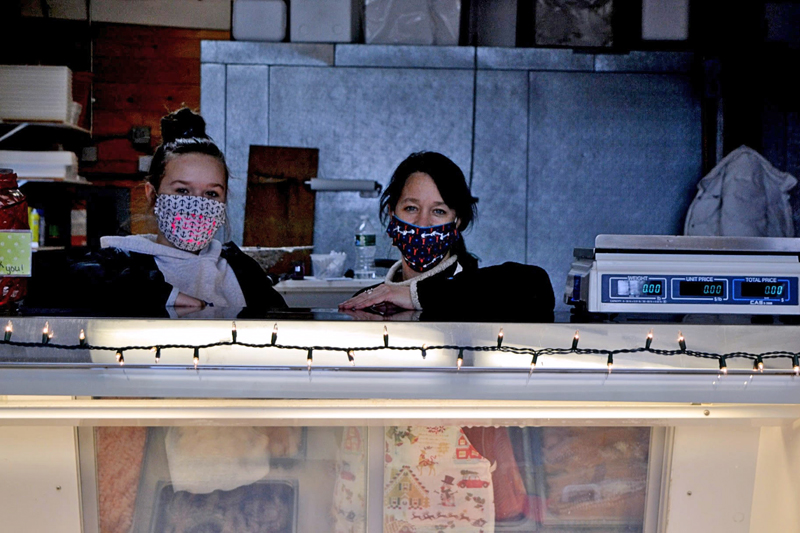 From left: daughter Sydney and mother Jamie Moore behind the counter at Fisherman's Catch Seafood Market in downtown Damariscotta. Jamie Moore owns the business. (Nettie Hoagland photo)
