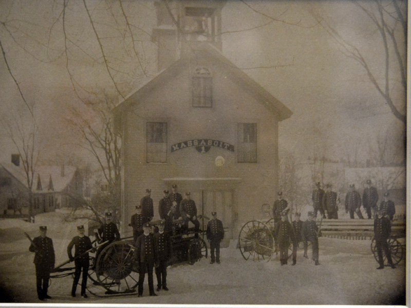The Massasoit firehouse on Feb. 22, 1900 with company members in uniform. Equipment includes a hose reel on skis for winter travel, the Massasoit hand tub, a hose reel, and the ladder truck. (Photo courtesy of the Ivan Flye Historical Photo Collection)