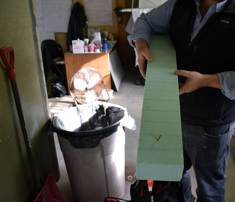 Ben Davis, owner of Nobleboro-based OpBox, demonstrates the sturdiness of a new material called EcoSIP that his company is using to create a mobile COVID-19 isolation unit for Sunday River Resort. EcoSIP is made from 100% recycled plastic bottles. (Evan Houk photo)