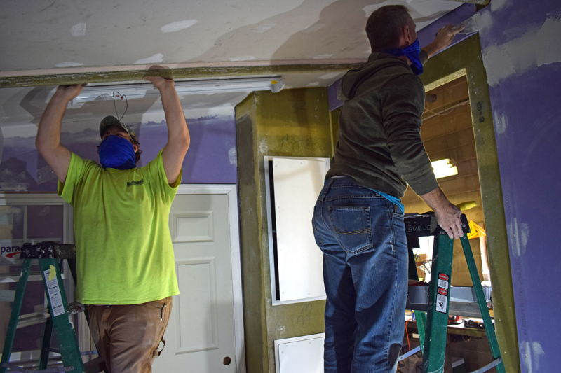 Sam Novak and Christian Kryger, employees of OpBox, construct a mobile COVID-19 isolation unit at the company's Nobleboro manufacturing facility on Tuesday, Dec. 29. (Evan Houk photo)