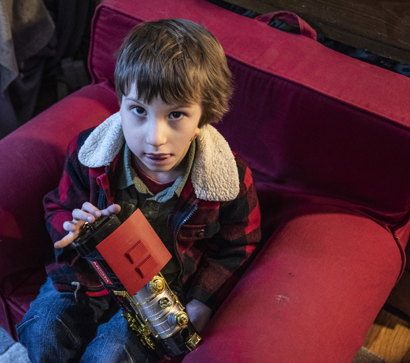 Hayden Libby, 5, holds a toy locomotive in Waldoboro on Saturday, Dec. 19. Libby's favorite toys are dinosaurs and anything with wheels. (Bisi Cameron Yee photo)