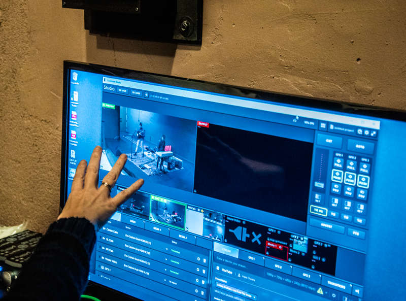 Kate Fletcher demonstrates the livestreaming system in the projection room at the Waldo Theatre in Waldoboro on Thursday, Dec. 3. The system has the ability to smoothly transition between three cameras that cover the extent of the stage. (Bisi Cameron Yee photo)