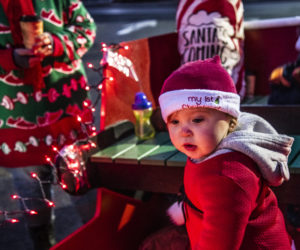 Magnolia Poulin, 14 months, explores the inside of the Renys sleigh during the Villages of Light reverse parade at Lincoln Academy in Newcastle on Saturday, Nov. 28. Magnolia delighted in waving at the hudreds of cars participating. (Bisi Cameron Yee photo)