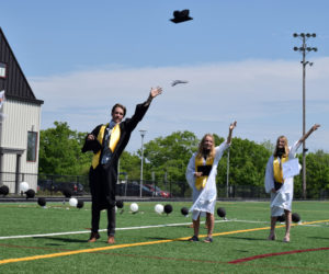 Lincoln Academy students from science teacher Matthew Buchwalder's advisory group toss their graduation caps in the air during a physically distant commencement ceremony on the William A. Clark Field in Newcastle on June 5. (Evan Houk photo)