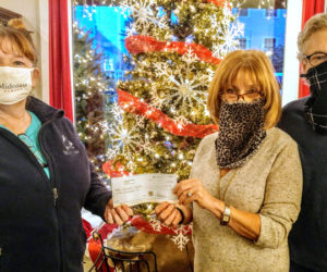From left: Tammy Walsh, of Midcoast Humane, accepts a check from Stars Fine Jewelry co-owners Frieda and John Hanlon.