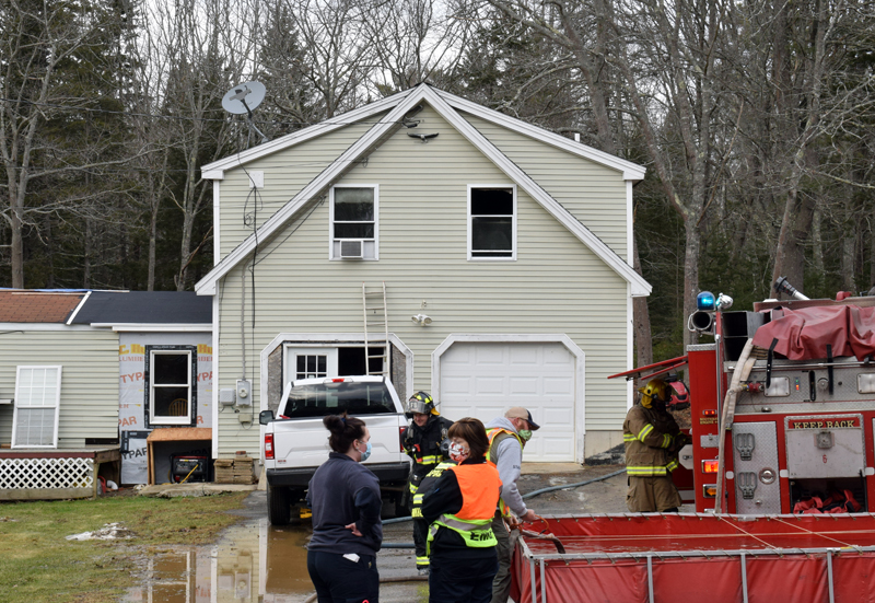 First responders work at the scene of a house fire at 21 West Side Road on Barter's Island, Boothbay, Thursday, Dec. 31. A dog and a cat perished from smoke inhalation, according to Boothbay Fire Chief Dick Spofford. (Evan Houk photo)