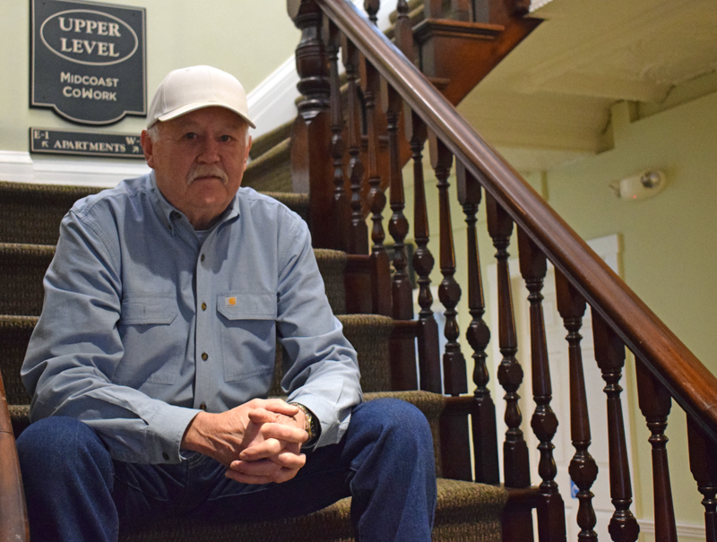 Ross Flood, owner of the Damariscotta Center building, sits on a staircase inside the 163-year-old structure on Dec. 22. Flood bought the building in 2000 and made extensive improvements to it. (Evan Houk photo)