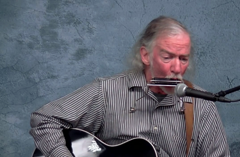 "Jon Couch wails on the harmonica and plays guitar for his rendition of ""Train of Glory"" during Damariscotta Open Mic's Peaceful New Beginnings show, available for streaming at lctv.org. (Screenshot by Evan Houk)"