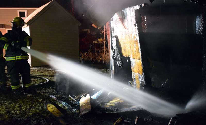 Firefighters soak the remains of a sauna behind a house at 153 West Old County Road in Newcastle the evening of Thursday, Jan. 21. The Newcastle Fire Department was able to extinguish the blaze within minutes of arriving and keep it from spreading to an adjacent shed or the house. (Evan Houk photo)