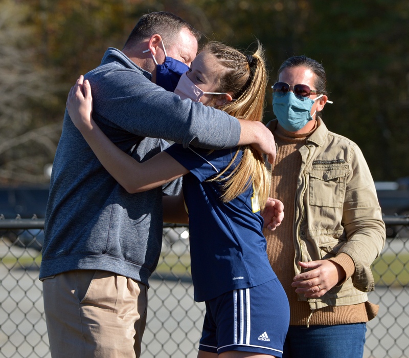 Medomak Valley High School senior Abby Lash hugs her father, MVHS Athletic Director Matt Lash, as her mother, Betsy Lash, looks on during the MVHS girls soccer team's senior recognition Oct. 9, 2020. (Paula Roberts photo, LCN file)