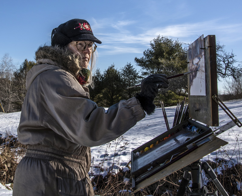 "Roberta Goschke paints a wintry scene in Waldoboro on Sunday, Jan. 10. Goschke ""suits up"" for plein-air painting sessions in winter. (Bisi Cameron Yee photo)"