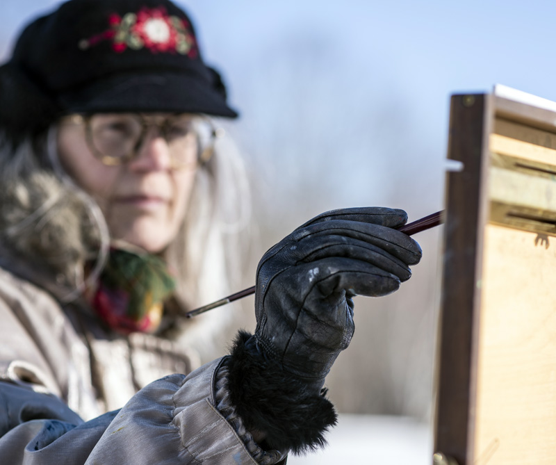 Roberta Goschke adds paint to a canvas  in Waldoboro on Sunday, Jan. 10. Her black leather gloves, supplemented by hand warmers, help her hold a brush in the cold air. (Bisi Cameron Yee photo)