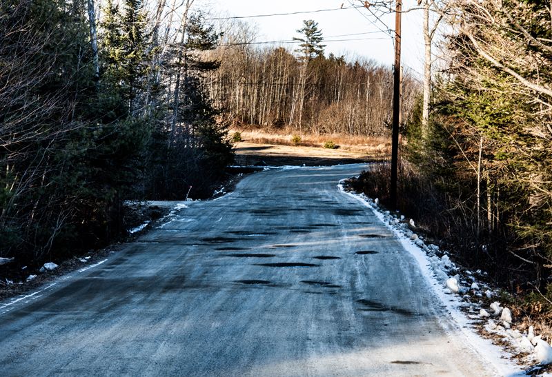 Potholes dot the gravel surface of Controversy Lane near its exit onto North Nobleboro Road in Waldoboro on Saturday, Jan. 23. (Bisi Cameron Yee photo)