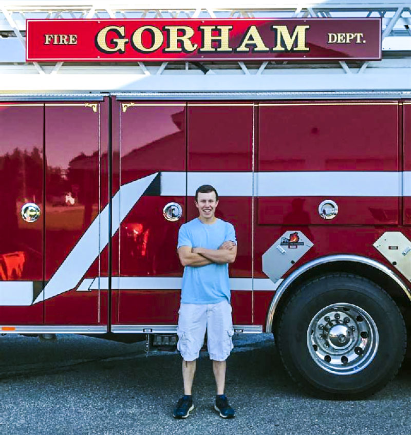 Oakley Oliver, of Jefferson, poses in front of a fire truck on his first day as a live-in trainee at the Gorham Fire Department. Oliver recently assisted in the rescue of an injured snowmobiler in Rangeley. (Photo courtesy Jen Oliver)