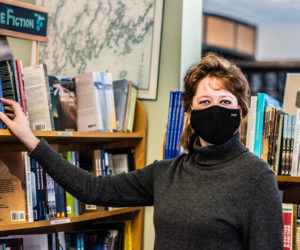Chloe Deblois adjusts the placement of a book at Sherman's Maine Coast Book Shop in Damariscotta on Sunday, Feb. 21. Deblois has worked for the store for 12 years and managed it for the last five. (Bisi Cameron Yee photo)