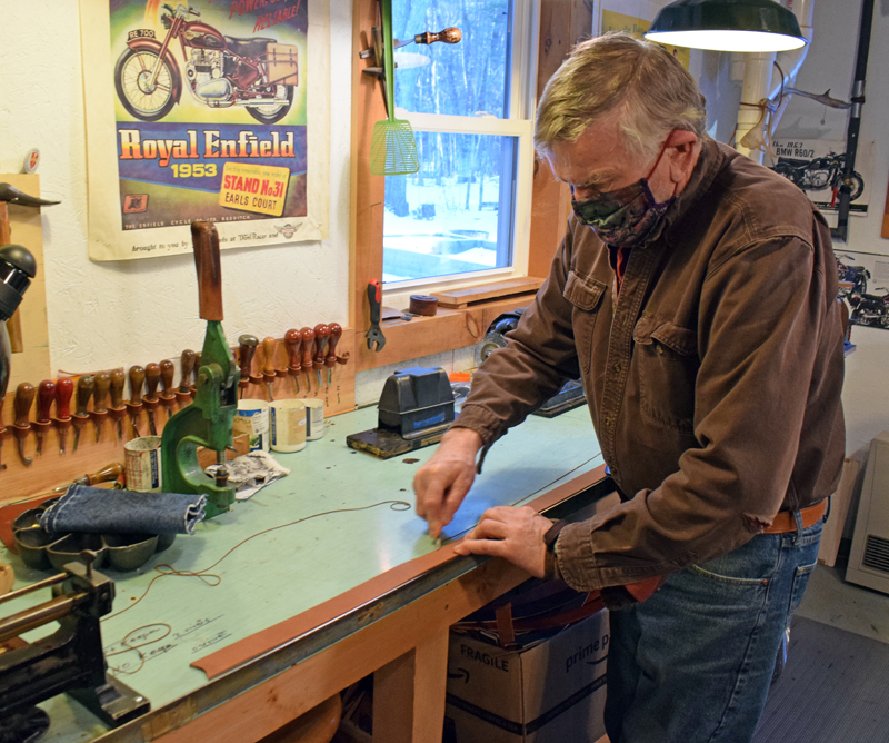 Narragansett Leathers owner Alan McKinnon trims a piece of leather for a belt at his home workshop in Newcastle on Jan. 7. McKinnon sells handcrafted leather goods at narragansettleathers.com. (Evan Houk photo)