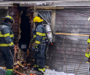Firefighters inspect the wall of a Nobleboro farmhouse after extinguishing a fire there Sunday, Feb. 7. An improperly installed pellet stove caused the fire, according to a Nobleboro Fire Department officer. (Photo courtesy Nobleboro Fire Department)