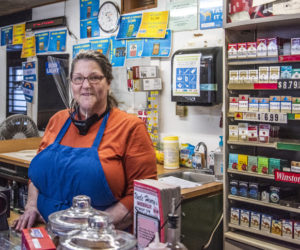 Nobleboro Village Store owner Joanne Kroll wears a face shield behind the counter of her store on Monday, Feb. 8. Kroll said the state suspended the store's license without proof that the store violated mask rules. (Bisi Cameron Yee photo)