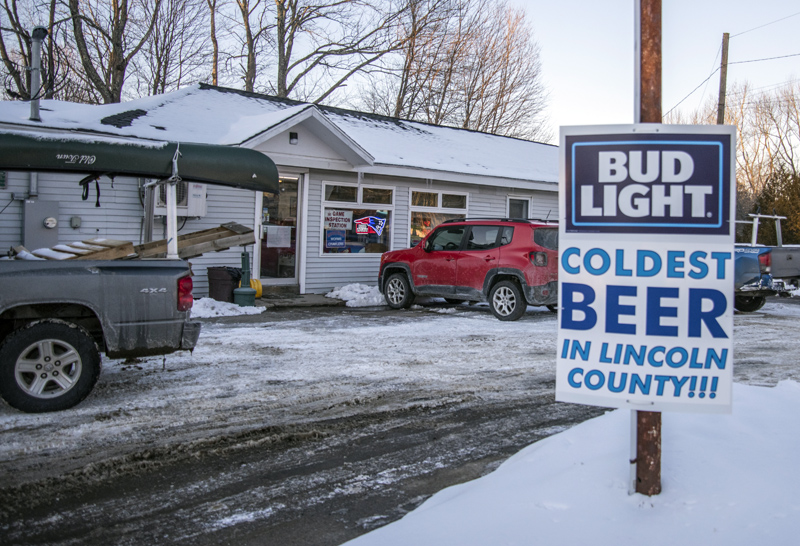 """A sign advertises the """"coldest beer in Lincoln County"""" at the Nobleboro Village Store on Monday, Feb. 8. The state temporarily closed the store, citing a failure to enforce mask-wearing. (Bisi Cameron Yee photo)"""