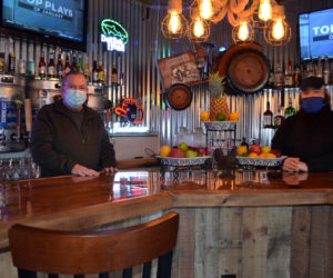 Dana Long (left) and Michael Collins stand behind the bar at the Barnhouse Grill & Pub in Wiscasset. Long and Collins own the restaurant with a third partner, Daniel Dyer. (Charlotte Boynton photo)