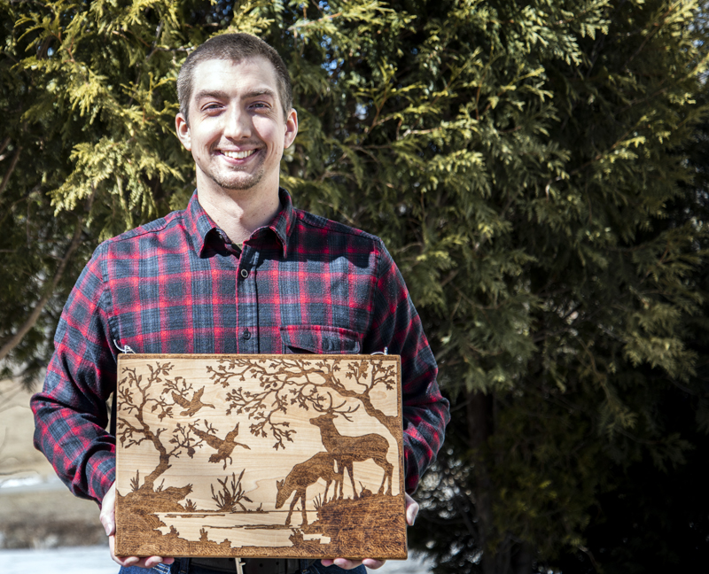 Tyler Richards displays an example of his woodburning technique on a cutting board in Damariscotta on Monday, March 8. Richards learned woodburning through trial and error and YouTube. (Bisi Cameron Yee photo)