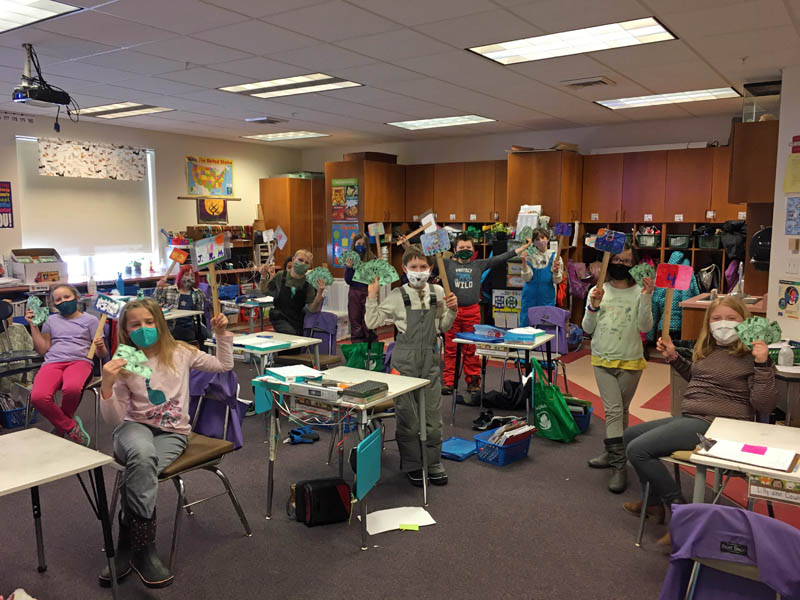 Students in Sarah Currier's fourth grade class at Edgecomb Eddy School hold up auction paddles and money, which they use in their classroom economy system. (Photo courtesy Sarah Currier)