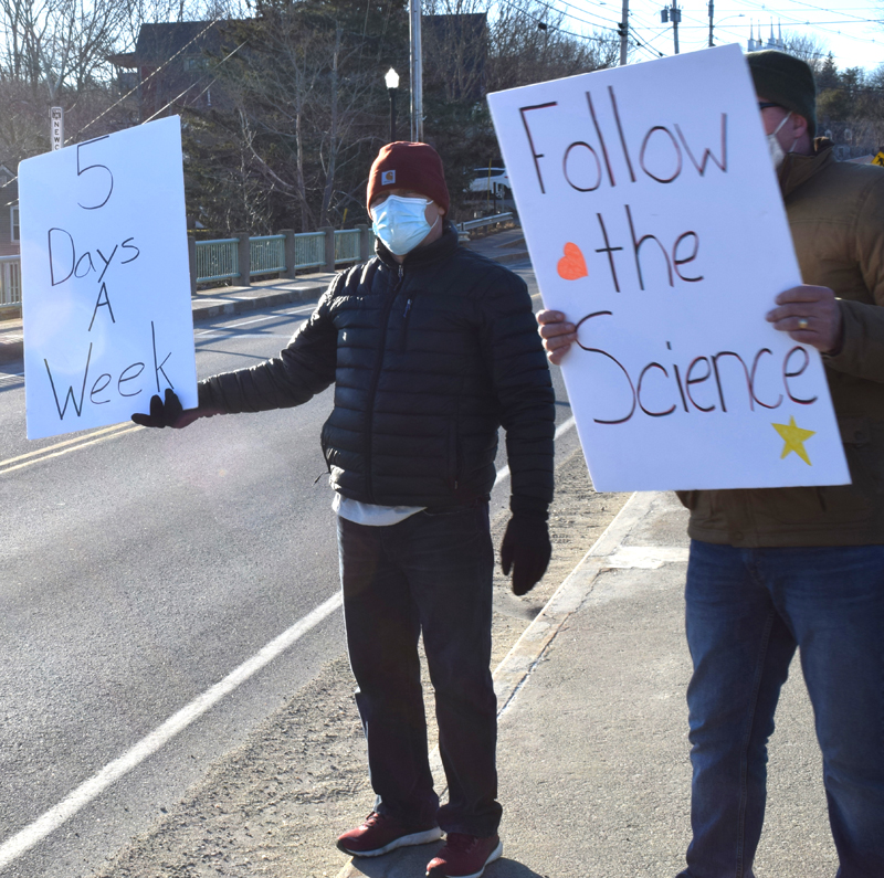Anthony Anderson, an LA parent and organizer of a demonstration on the Twin Villages bridge, holds a sign expressing support for a return to full-time, in-person instruction at Lincoln Academy on Saturday, March 13. (Evan Houk photo)