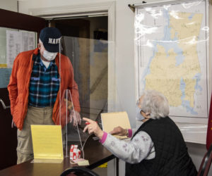 Bob Nelson receives his ballot from Nancy Hartford in Nobleboro on Friday, March 19. Nelson was among the first voters to arrive at the polls for the annual town meeting by referendum. (Bisi Cameron Yee photo)