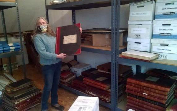 Bristol Town Clerk Rachel Bizarro holds a tax assessment ledger book in front of racks of old town records that are slated to be moved to the shared vault under construction at the Bristol History Center. (Photo courtesy Chris Hall)