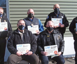 Local law enforcement receive LTIP decals to promote new tip line number. Front row, from left: Lincoln County Sheriff's Office Chief Deputy Rand Maker, Sgt. Perry Hatch of Wiscasset Police Department. Back row, from left: Sheriff Todd Brackett, Damariscotta Police Chief Jason Warlick, Officer Lawrence Brown of Boothbay Harbor Police Department, and Waldoboro Police Chief John Lash.