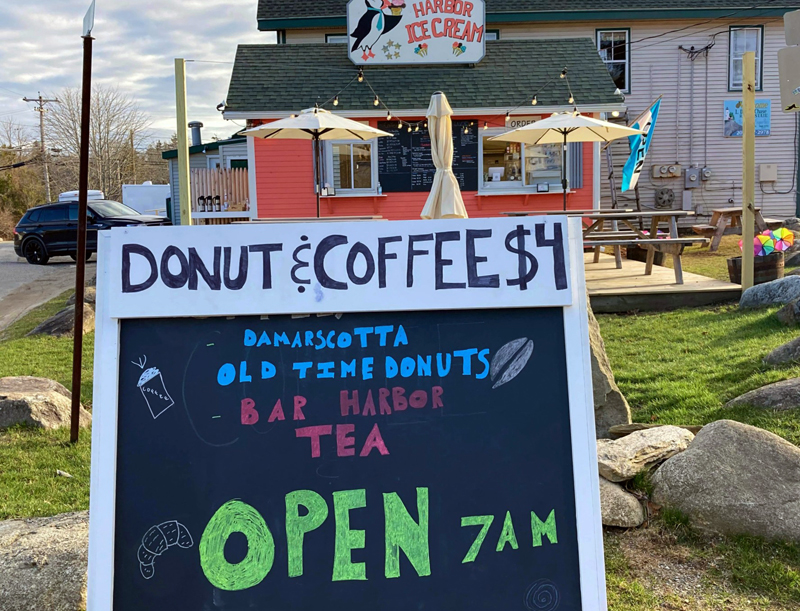 A sign advertises local food and drink at Harbor Ice Cream and Cafe on the Hill, Tuesday, April 6. The business opened for the season Saturday, April 3. (Nettie Hoagland photo)