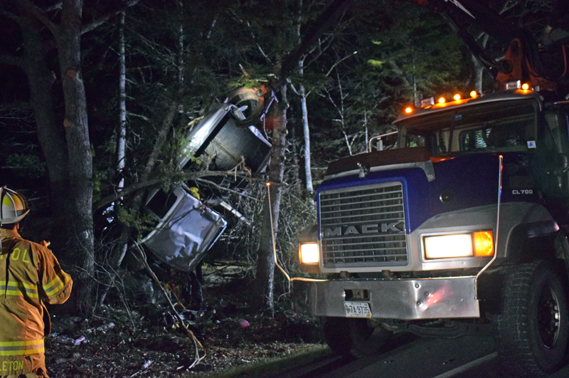 A pulp truck operated by Joe Winchenbach works to free a pickup truck from trees off Bristol Road near Pemaquid Falls late Tuesday, April 13. (Evan Houk photo)