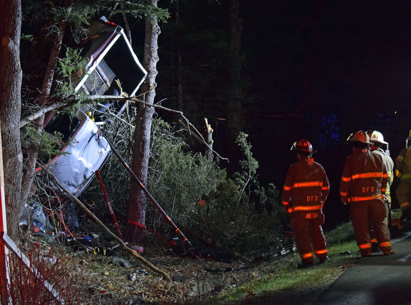 Firefighters inspect a truck trapped bed-up in trees off Bristol Road in Pemaquid late Tuesday, April 13. (Evan Houk photo)