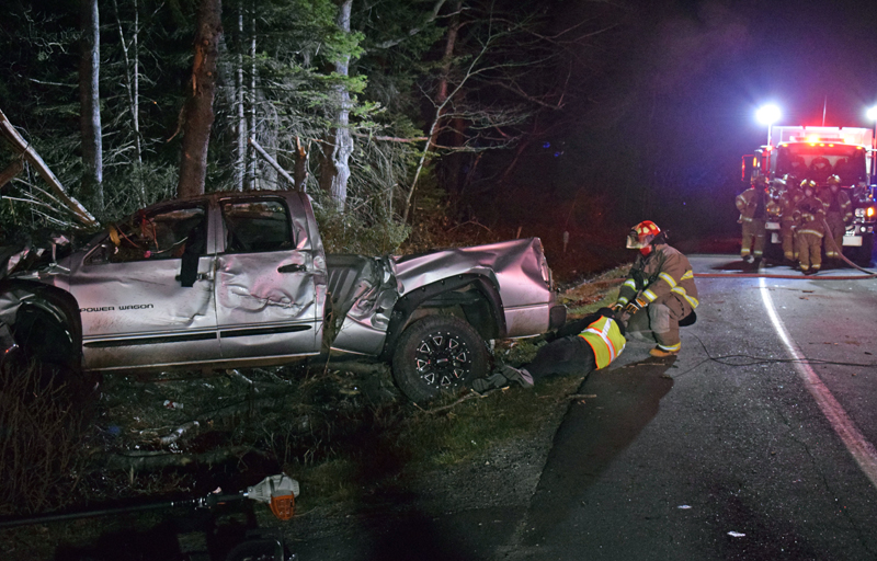 Dennis Hoppe, of Quick Turn Auto Repair and Towing, and Damariscotta firefighter John Knof work to tow a pickup truck out of a ditch off Bristol Road in Pemaquid after a pulp truck freed it from some trees late Tuesday, April 13. (Evan Houk photo)