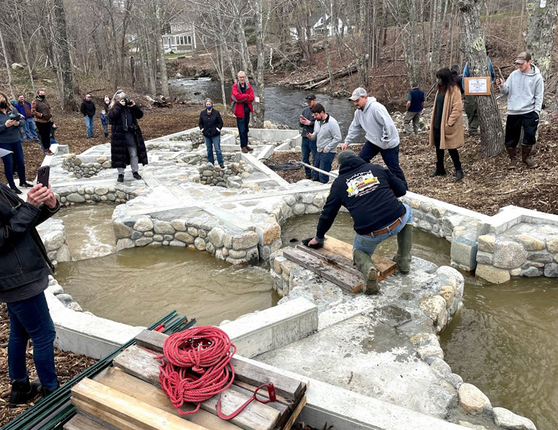 Bristol Fish Committee member Rick Poland removes debris from the new Bristol Mills fish ladder as a small crowd watches water from the Pemaquid River flow through the ladder for the first time on Sunday, April 18. (Evan Houk photo)