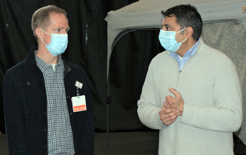 From left: Andrew Russ, associate vice president of medical affairs at LincolnHealth, talks with Nirav Shah, director of the Maine Center for Disease Control and Prevention, during a surprise visit to the Boothbay Region YMCA's Marylouise Tandy Cowan Fieldhouse in Boothbay Harbor on Saturday, April 10. (Photo courtesy John Martins)