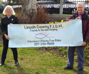 Terri Taylor (left) and Edie Vaughan hold a banner for Lincoln County Friends in Service Helping, also known as LC FISH. Vaughan has stepped down as the head of the program, which Taylor will now lead.