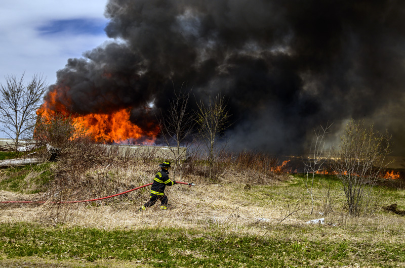 A firefighter heads toward a secondary fire after wind spread flames from a barn to a nearby field during a training exercise in Nobleboro on Saturday, April 24. (Bisi Cameron Yee photo)